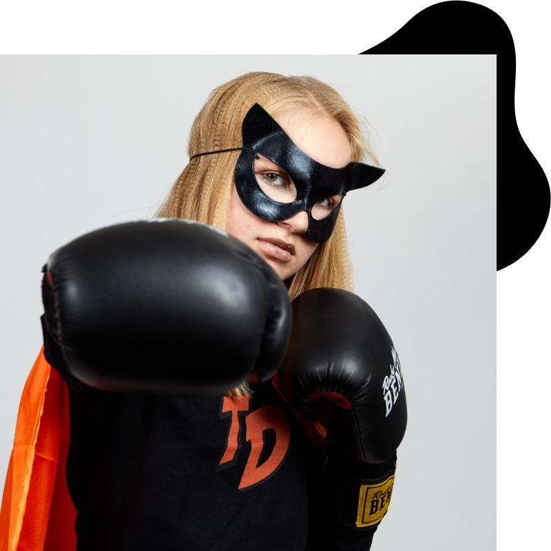 """Jugendlicher mit """"BOOM KPI"""" Schild in der Hand und Superheldenmaske vor den Augen"""